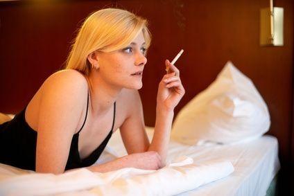žena kouří v posteli