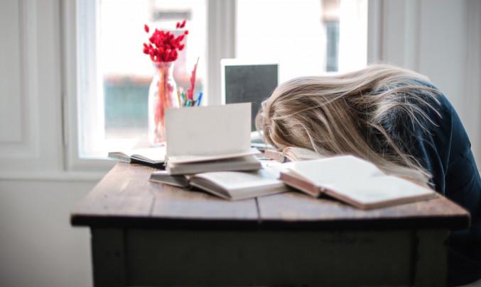 Vyčerpaná žena s hlavou na stole