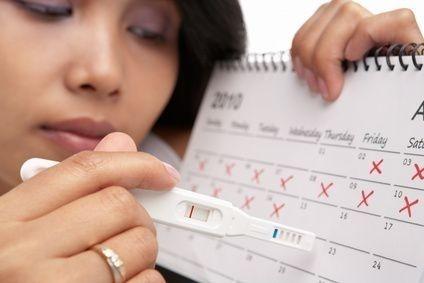žena u kalendáře s těhotenstkým testem