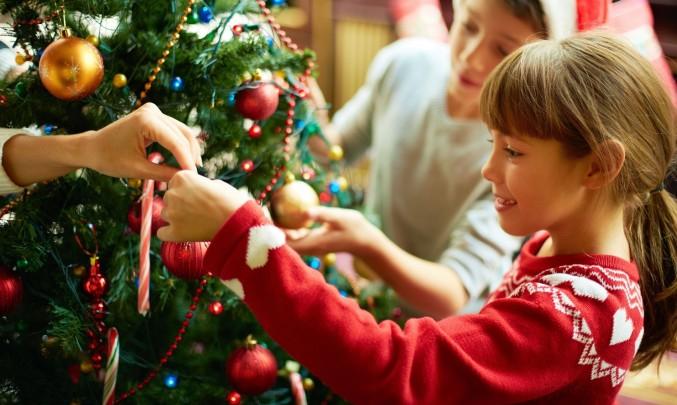 dítě zdobí vánoční stromeček