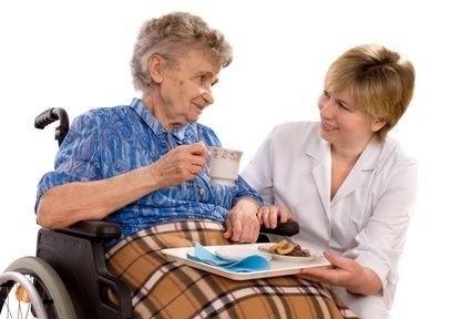 stará paní na vozíku s pečovatelem