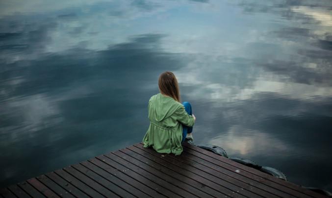 Osamělá dívka sedí na molu