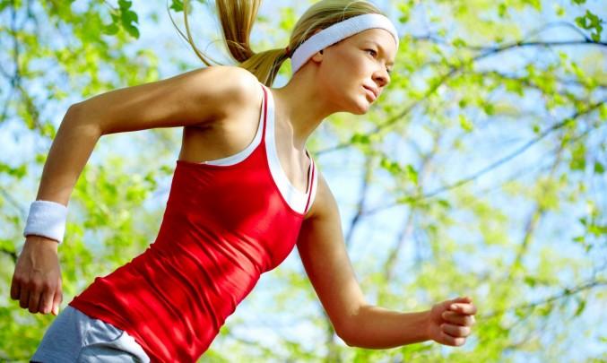 žena v červeném tričku běží v parku