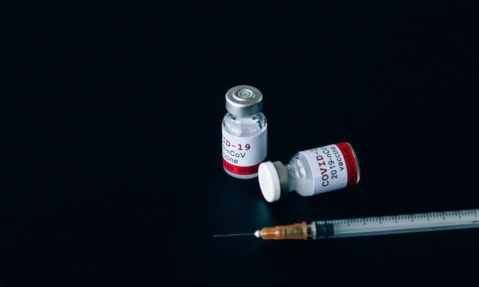 Ampule s vakcínou proti covid-19 a inječkní stříkačka