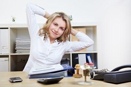 pani u stolu v kancelari se protahuje