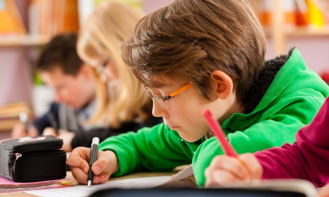 školák se soustředí na psaní