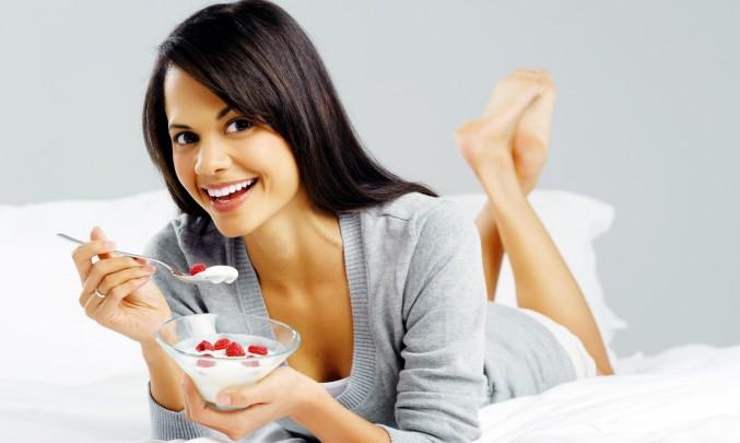 slečna jí bílý jogurt s jahodama na posteli