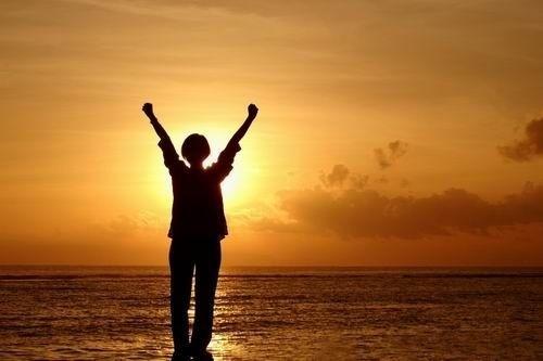 Západ slunce u moře a protahující se osoba