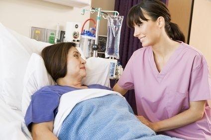 ležící žena v nemocni s ošetřovatelkou