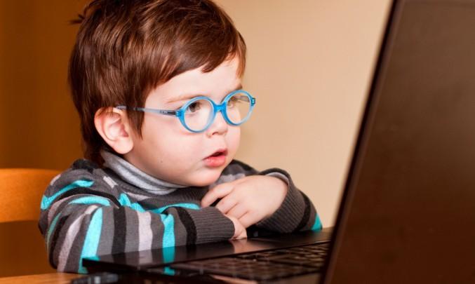 dítě s brýlemi před laptopem