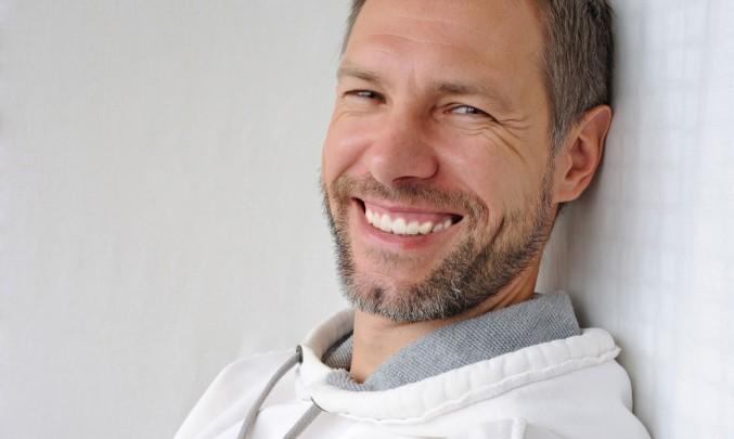 muž s vousy se zubí