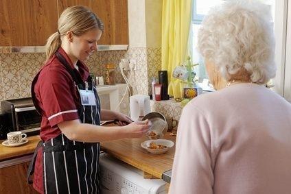 pečující žena připravuje jídlo seniorce