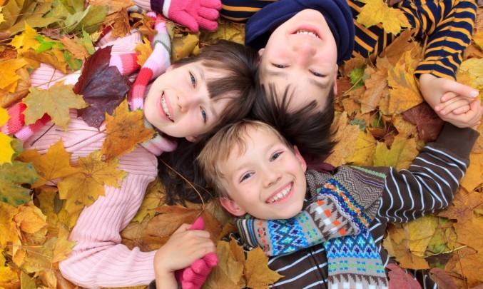 děti leží ve spadaném listí