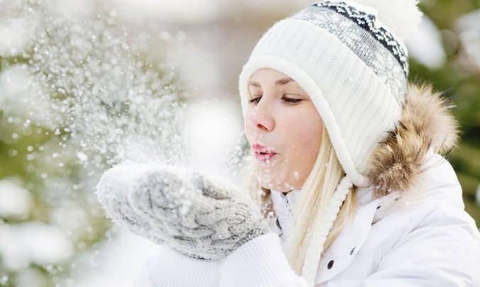 žena fouká do sněhových vloček