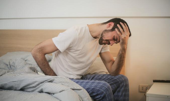 Smutný muž v pyžamu sedící na posteli