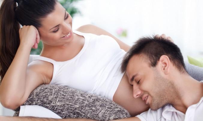 těhotná žena a muž s hlavou na břiše