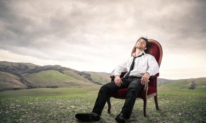 přepracovaný muž sní o přírodě, zatímco sedí v kanceláři