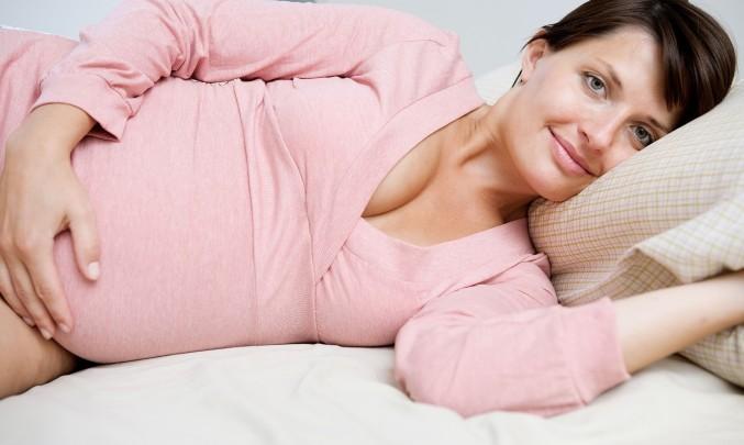 těhotná žena leží v posteli