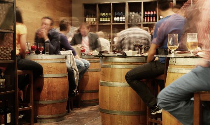 Lidé sedící v hospodě u stolů s alkoholem
