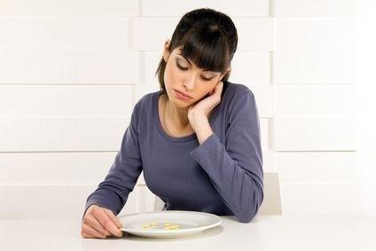 dívka nad talířem s léky, hlad, příprava na operaci