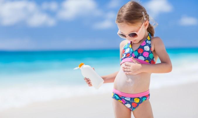 holčička se maže opalovacím krémem na pláži u moře