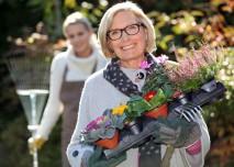 žena zahradnice si nese květiny
