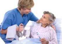 ležící pacientka vykonává hygienu s pomocí zdravotní sestry