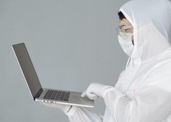 Lékař v ochranných pomůckách s notebookem