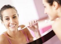 hezká mladá žena si čiští zuby v koupelně