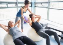 dvě ženy cvičí na míči a třetí je opravuje