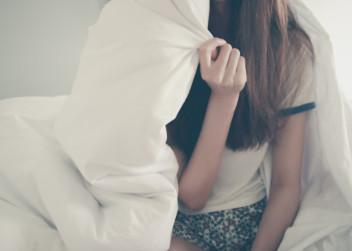 Dívka sedí na posteli pod peřinou