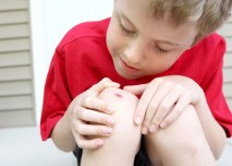 chlapec s odřeným kolenem