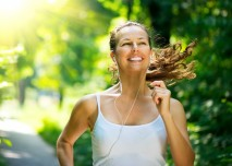 mladá žena běží v parku s úsměvem na rtech