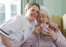 seniorka pije čaj, pečovatelká sedí vedle ní