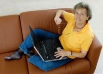 žena sedící na gauči s notebookem