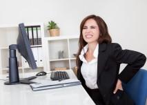 žena s bolestí zad za kancelářským stolem