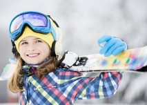 lyžařka si nese lyže