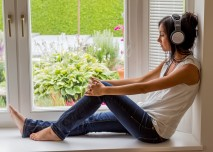 dívka poslouchá hudbu v okně