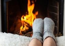nohy v teplých ponožkách u krbu
