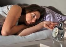 žena nemůže spát a kouká na budík