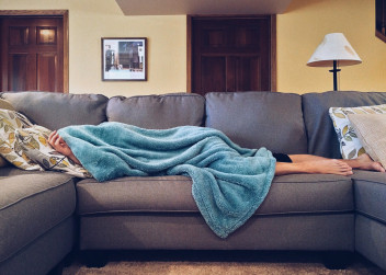 Unavená žena leží na gauči přikrytá dekou
