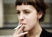 žena kouří balenou cigaretu