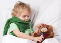 dítě s horečkou měří teploměrem plyšového medvěda