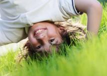 dítě hlavou dolů v trávě
