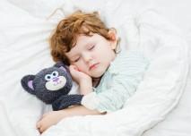kluk spí s plyšákem v posteli