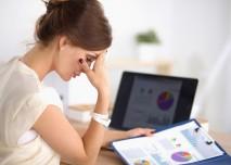 žena sedí v práci nad grafy a má toho dost
