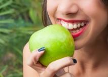 žena se chystá zakousnout do jablka