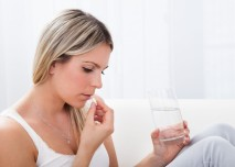 mladá žena si bere prášek na bolest