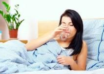 žena pije vodu v posteli