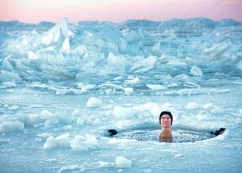 Otužilec ve zmrzlé vodě s kusy ledu